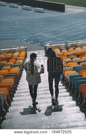 Two Young Sportswomen With Sport Bottles On Stadium Stairs