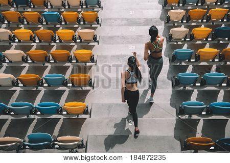 Two Sportswomen Running On Stadium Stairs, Running Women Concept