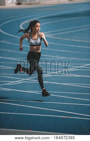 Athletic Young Sportswoman Sprinting On Running Track Stadium