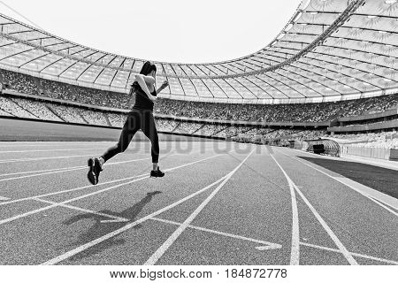 Back View Of Young Fitness Woman In Sportswear Sprinting On Running Track Stadium, Black And White P
