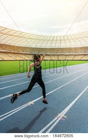 Athletic Young Woman In Sportswear Sprinting On Running Track Stadium At Sunset