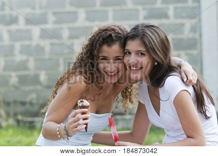 Hispanic friends hugging and eating ice cream together