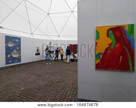 KIEV - UKRAINE - MAY 2017: Kiev Art Fort 2017. Visitors are viewing the exposition of the exhibition. On the wall hangs an eccentric portrait of a young woman