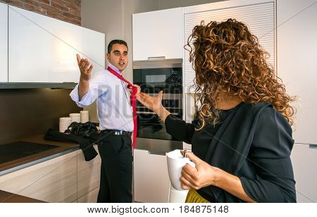 Angry young businessman arguing with curly woman at home while knotting his tie