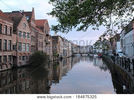 GENT, BELGIUM, APRIL 07 2017: Evening view of the water and historic buildings from the Kraanlei in Gent. Gent has a historic city centre and is a hugely popular tourist destination in East Flanders.