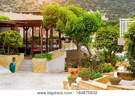 Modern and classic resort Greek architecture. Landscaping and gardening local area. White building of houses stands on shore of Cretan sea. Resort village Bali Rethymno