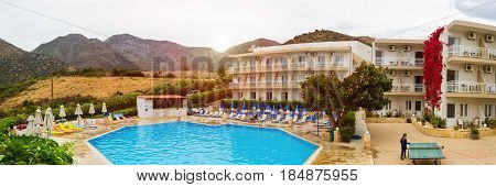 Bali Greece - May 2 2016: Relax and sunbathe by pool with clear blue water in Resort hotel Atali Village 4 star. Empty pool without tourists early morning at hotel. Bali Rethymno Crete Greece