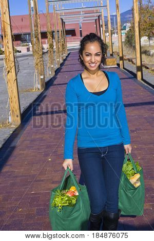 Mixed race woman carrying groceries in reusable bag