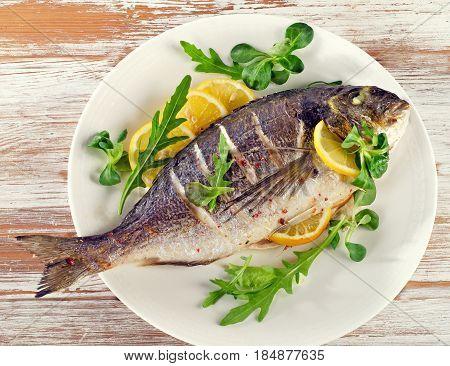 Fried Sea Bream On Plate With  A Lemon.