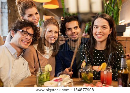 leisure, technology, friendship, people and holidays concept - happy friends with food and drinks and taking picture by smartphone selfie stick at bar or cafe