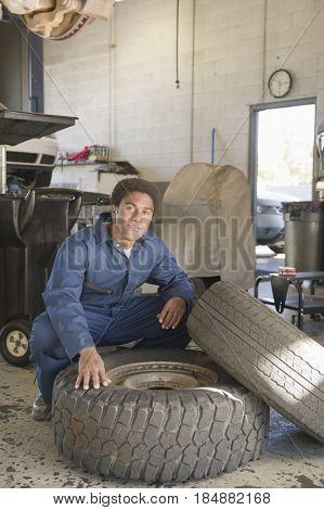 Mixed race mechanic checking tire in auto repair shop