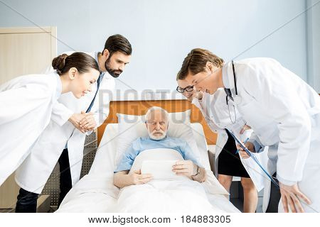 Professional young doctors looking at senior patient using digital tablet in hospital bed elderly patient with doctors concept