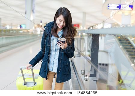 Woman go travel and using cellphone checking for flight in airport