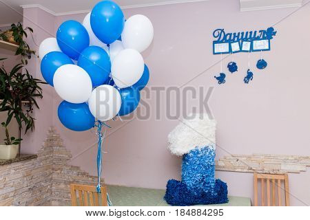 The child is one year old. Bright children's room decorated with balloons, a toys and a large number one of colored paper.