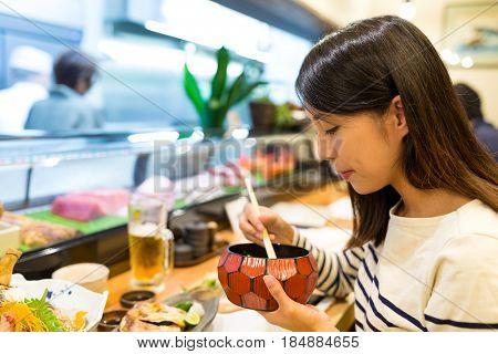 Woman having dinner in japanese restaurant