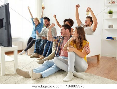 friendship, people and entertainment concept - happy friends drinking beer or cider and watching tv at home