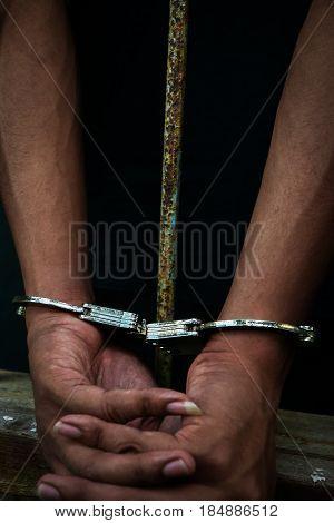Hand of the prisoner on a steel lattice close up Un-freedom concept.