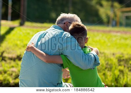 family, generation, relations and people concept - happy grandfather and grandson hugging outdoors