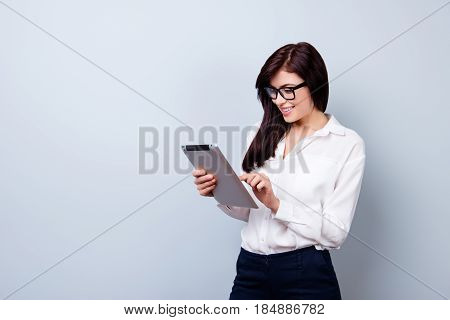 Pretty Young Worker Woman In Formal Clothing And Glasses Holding Digital Tablet And Looking For Some