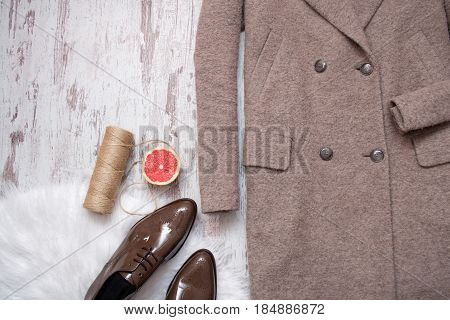 Part Of Brown Coat And Brown Patent Leather Shoes, Grapefruit And Twine, Wooden Background. Fashion