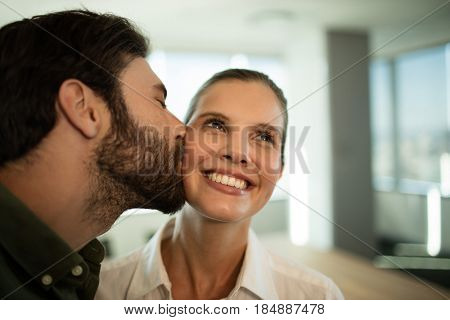 Close up of businessman kissing businesswoman in office
