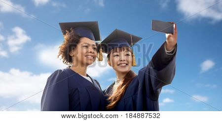 education, graduation, technology and people concept - group of happy international students in mortar boards and bachelor gowns taking selfie by smartphone over blue sky and clouds background