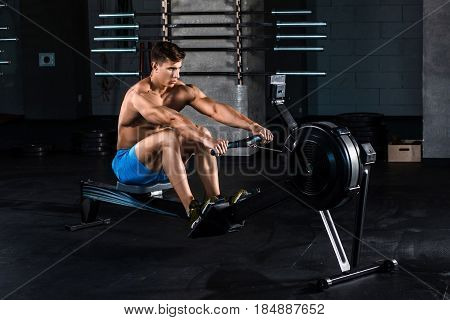 Muscular man doing exercise for legs in the gym. The athlete is in good shape. Personal trainer