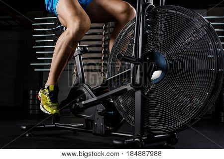 Intense cardio workout. Side view close-up part of young man in sports shoes cycling at gym. Muscular man. Part of the body