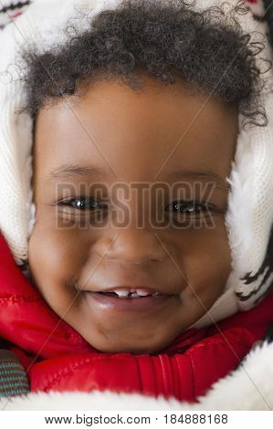 Grinning African American baby in cap