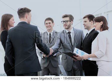 investor and CFO in the presence of a business team shake hands