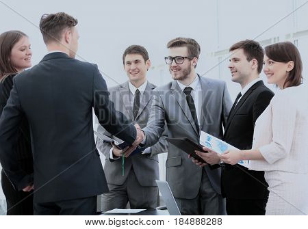 business partners in the presence of a business team shake hands