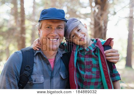 Portrait of happy father and son with arm around in forest