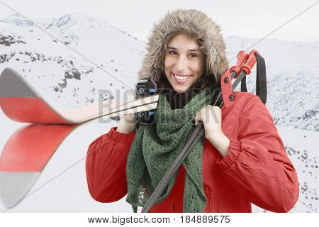 Mixed race woman carrying skis and poles