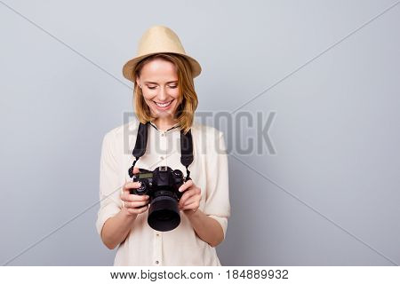 Portrait Of Pretty Young Photographer In Straw Hat Holding Camera And Checking Photos