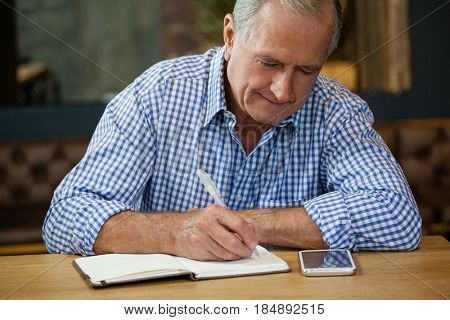 Senior man writing on diary at table while sitting in cafe