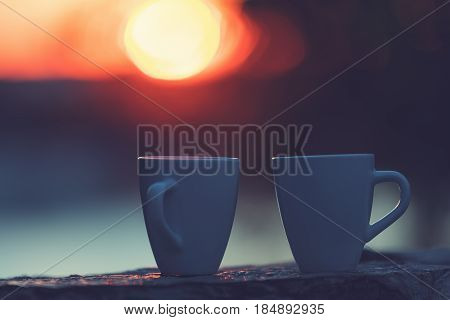 Silhouettes of two coffee cups in sunset / sunrise. Shallow depth of field.