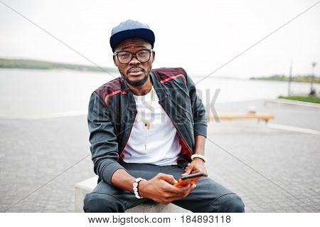 Portrait Of Stylish African American Man On Sportswear, Cap And Glasses Sitting At Stone Cube With P
