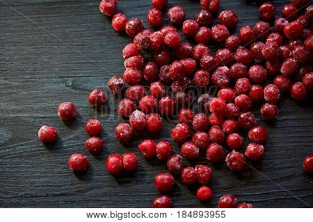 A lot of frozen cherry without sticks on a wooden black background.Vitamins and a healthy diet