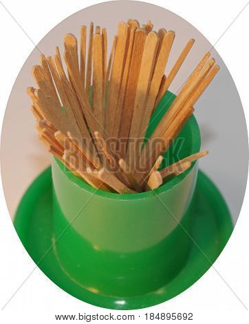 Wood toothpicks in a green plastic holder.