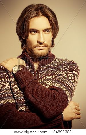 Handsome man wearing winter pullover. Men's beauty, fashion. Hairstyle for men. Studio shot. Sepia style.
