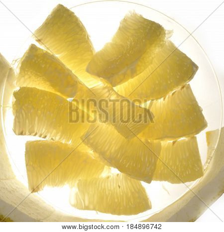 Peeled slices pomelo fruit on a glass plate