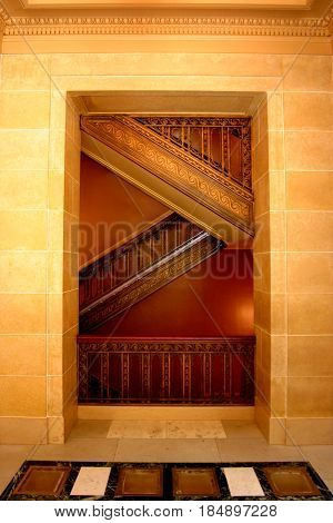 A staircase criss-crosses up, framed by hundred year old masonry work at the capitol building in Madison, Wisconsin