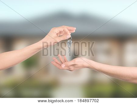 Hands with keys with house on background