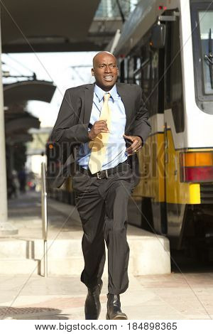 African American businessman running for train