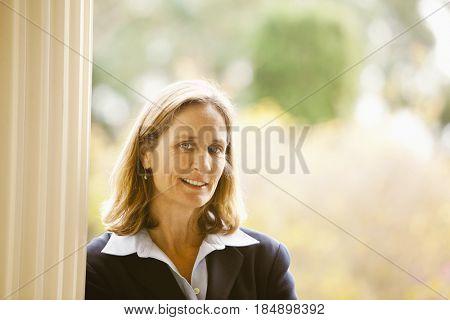 Caucasian businesswoman leaning against post