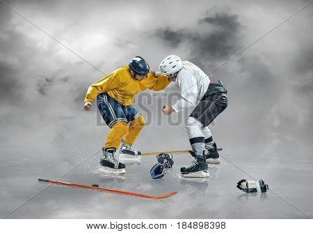 Two Ice hockey players in boxing action on the ice under sky with clouds, outdoors