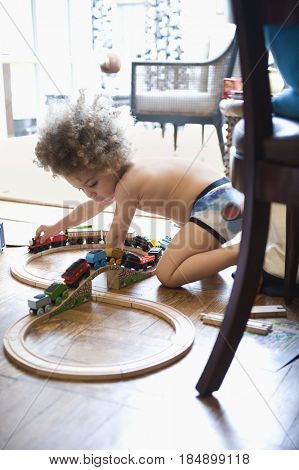 Mixed race boy playing with toy train