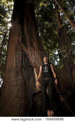 Caucasian man standing on roots of large tree