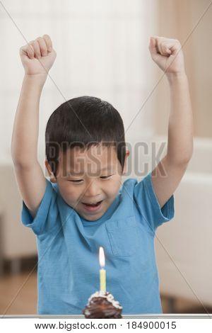 Excited Korean boy looking at birthday cupcake
