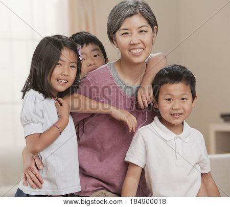 Asian mother sitting with children